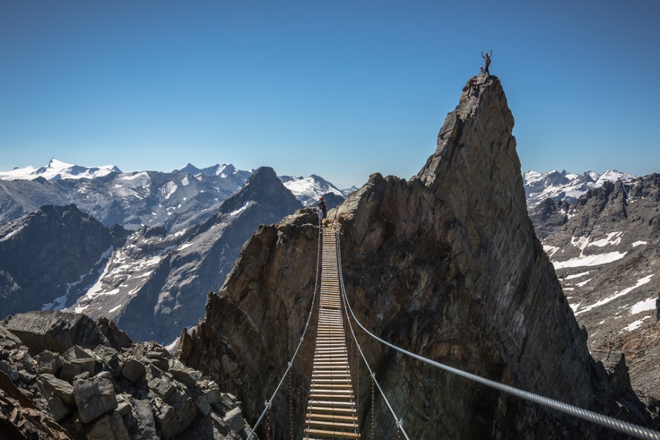 A climber stands on a sunny peak with a long suspension bridge in the foreground at CMH Bobbie Burns in British Columbia, Canada.