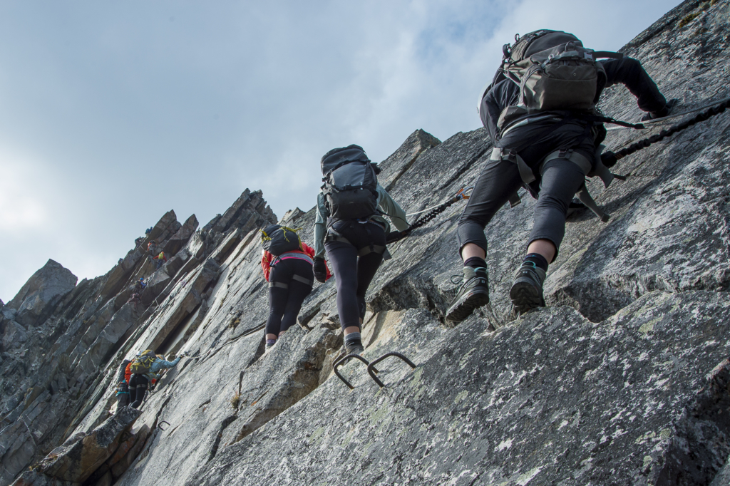Climbers ascend a rock wall on the Skyladder via ferrata at CMH Bugaboos.