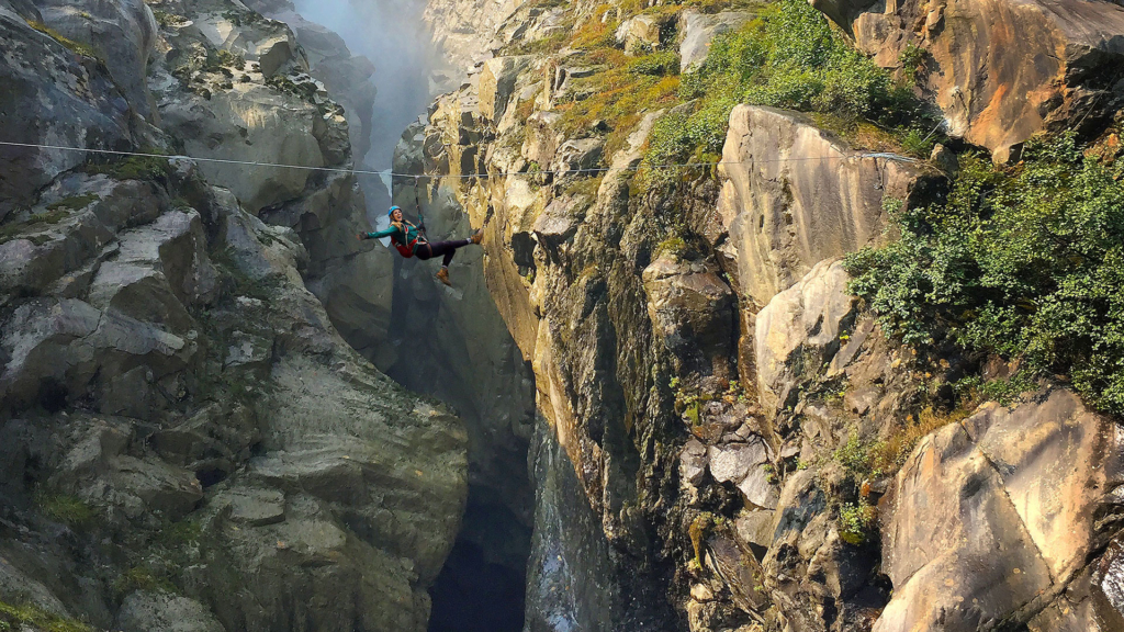 A female zip-lines across a deep canyon on a via ferrata, with rushing water underneath as she crosses the river at CMH Cariboos.